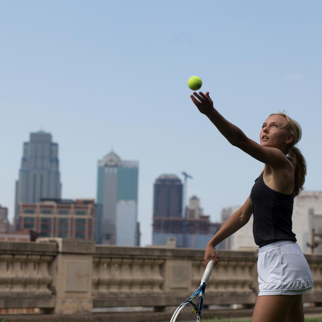 Member of the women's tennis team practices her serve at a park in Kansas City, with the skyline behind her