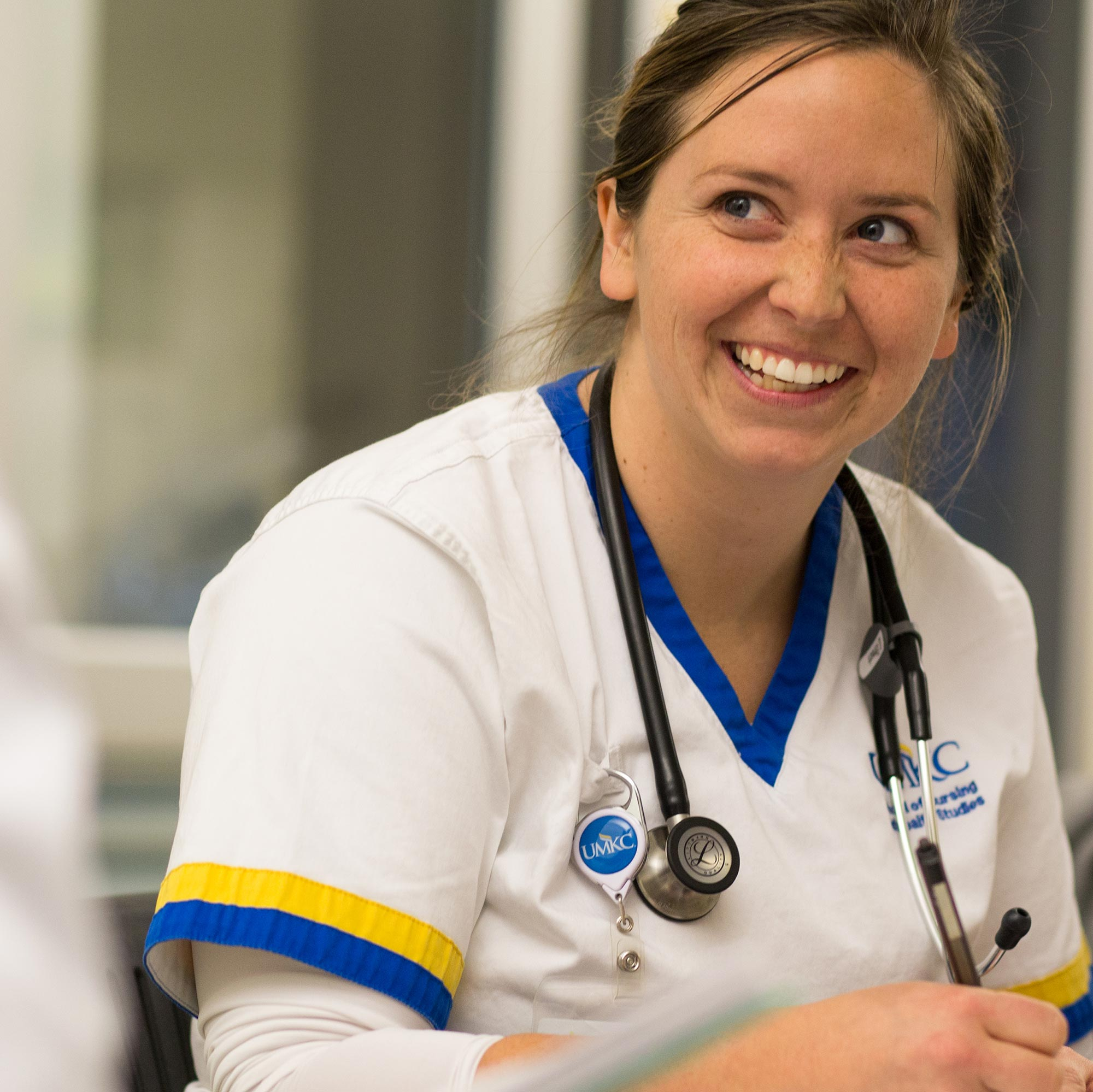 Nursing student writes notes on a chart and smiles while participating in a simulation event