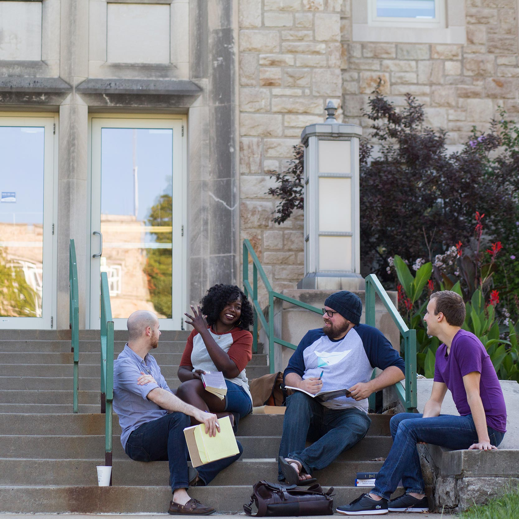 Students sit on the stairs in front of a UMKC academic building